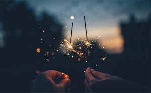Two hands holding sparklers at dusk