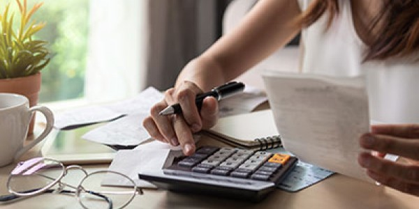 Woman using calculator and holding receipts
